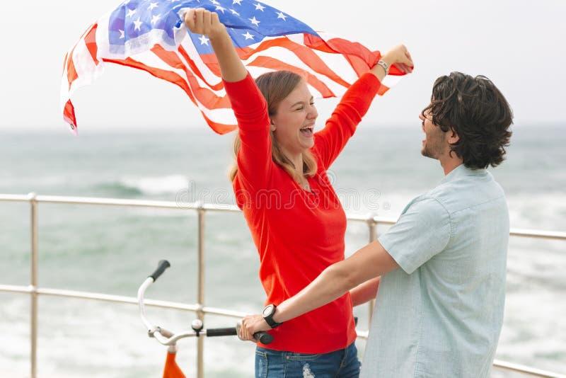 Romantiska Caucasian par som står på promenad, medan rymma amerikanska flaggan fotografering för bildbyråer