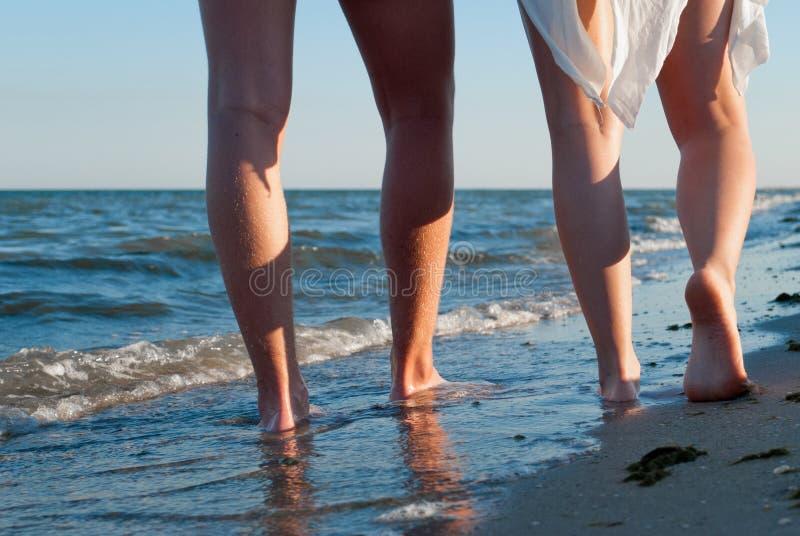 Romantiska datumman- och kvinnligben som promenerar kusten arkivfoton