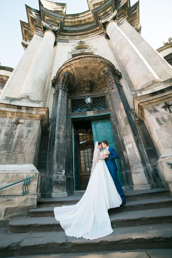 Romantiska eleganta nygift personpar som poserar nära barock kolonn, kyrktar arkivfoton