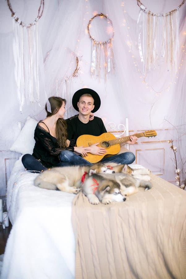 Romantiska gladlynta par som vilar den hemmastadda spela gitarren man som spelar gitarren för hans älskade flicka fotografering för bildbyråer