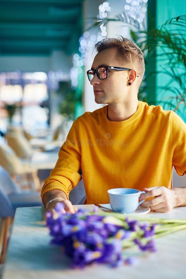 Romantiska Guy Waiting för datum i kafé arkivfoto