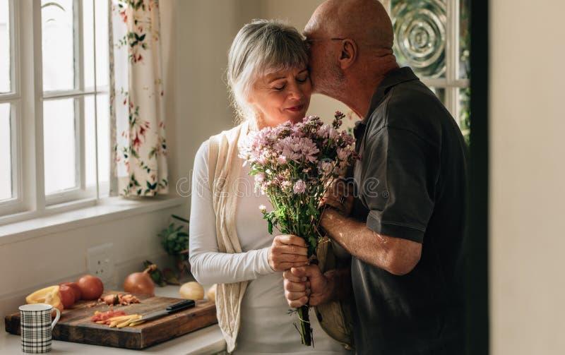 Romantiska höga par hemma som uttrycker deras förälskelse royaltyfri fotografi
