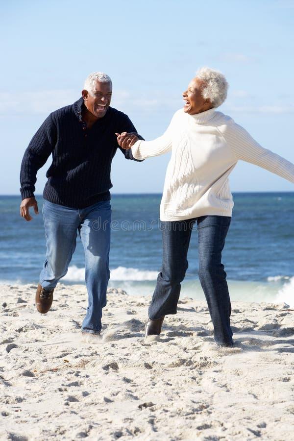 Romantiska höga par som kör längs strand royaltyfria bilder