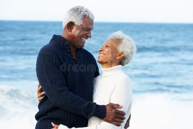 Romantiska höga par som kramar på strand arkivfoto