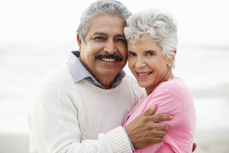 Romantiska höga par som kramar på strand royaltyfri fotografi