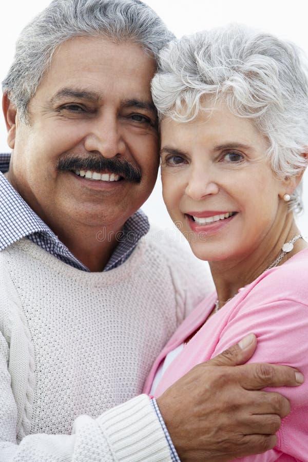 Romantiska höga par som kramar på strand royaltyfri bild