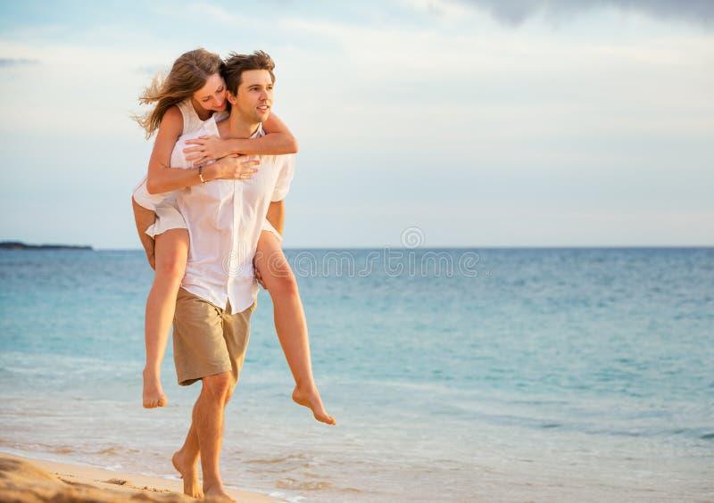 Romantiska lyckliga par på stranden på solnedgången royaltyfri bild