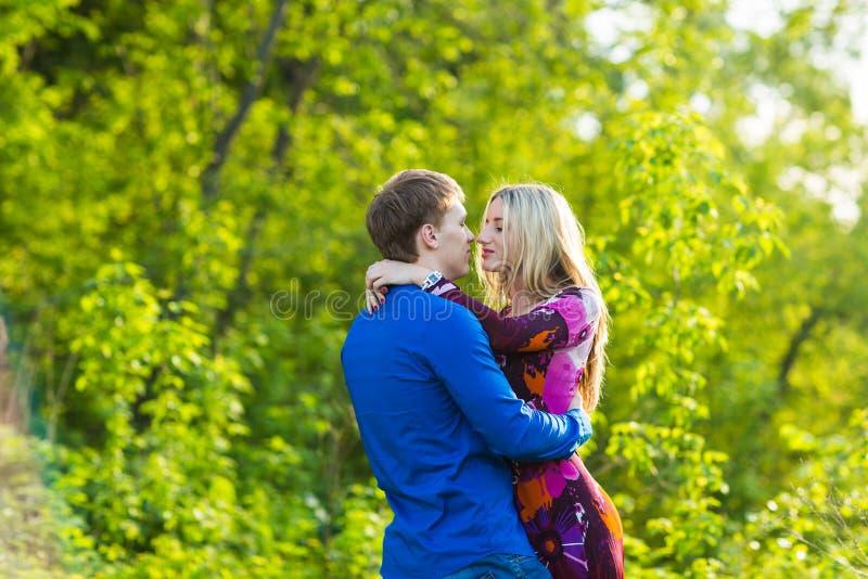 Romantiska lyckliga par som är förälskade på naturen Mannen och kvinnan som kysser i sommar, parkerar arkivfoto