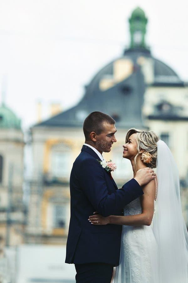 Romantiska nygift personpar som framme kramar av gammal kyrka royaltyfri bild