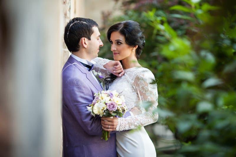 Romantiska nygift personpar som kramar nära den gamla byggnadsväggen arkivfoton