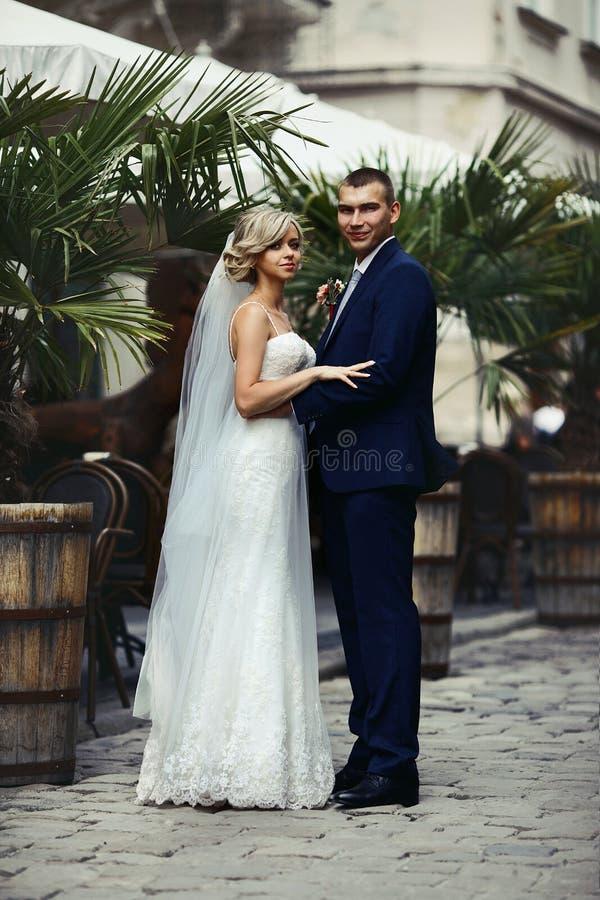 Romantiska nygift personpar som kramar nära exotisk restaurang arkivfoto