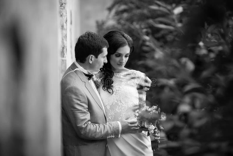 Romantiska nygift personpar som kramar nära gammal byggnadsväggb&w arkivfoton