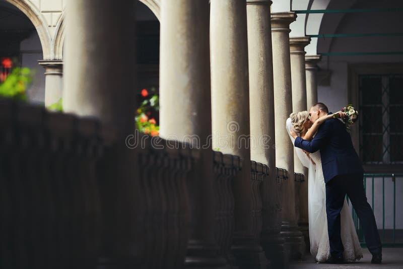 Romantiska nygift personvalentinpar som kysser på antika balkongwi royaltyfri fotografi