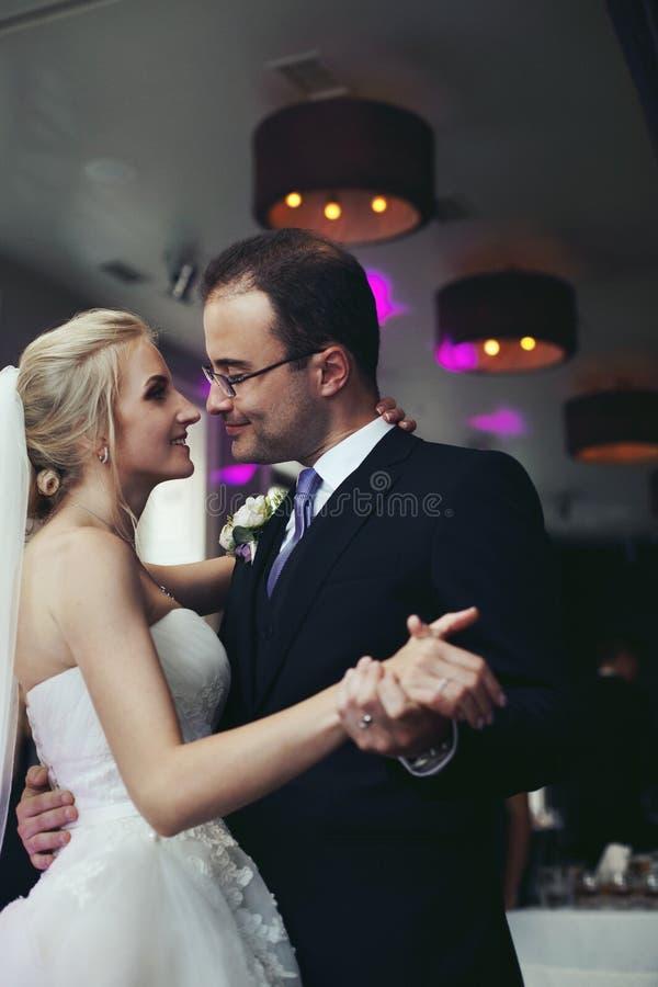 Romantiska nygifta personer, bruden och brudgummen dansar först och att rymma händer, royaltyfria bilder