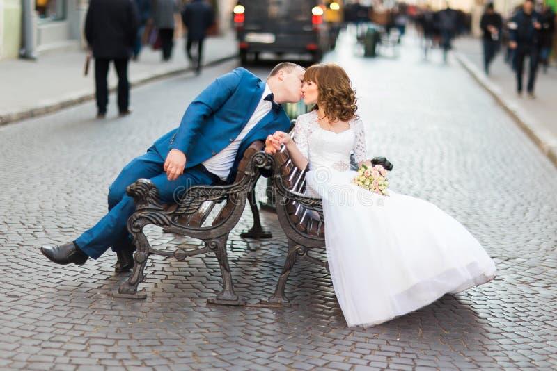 Romantiska nygifta personer som kysser och sitter på träbänk i gammal stad royaltyfri fotografi