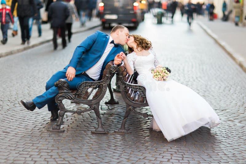 Romantiska nygifta personer som kysser och sitter på träbänk i gammal stad royaltyfri foto