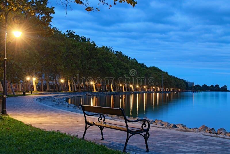 Romantiska och fredliga scener Tom bänk belyst med lamppost Morgonlandskapsvy av sjön Balaton och trädspaley royaltyfri bild