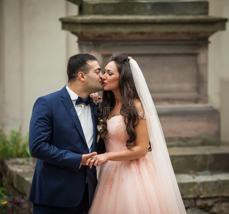 Romantiska par av nygifta personer som rymmer händer och kysser med en mo royaltyfri bild