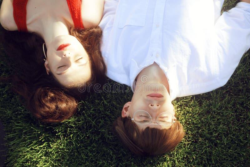 Romantiska par av ungdomarsom ligger p? gr?s parkerar in Lyckliga par som kopplar av med ögon, stängde sig r?da flickakanter Mode royaltyfri fotografi