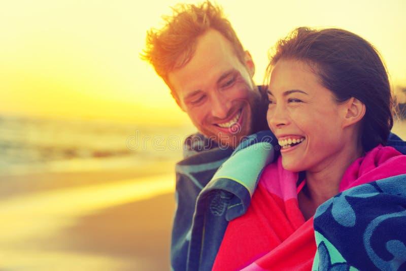 Romantiska par för badning med handduken på strandsolnedgång royaltyfri bild