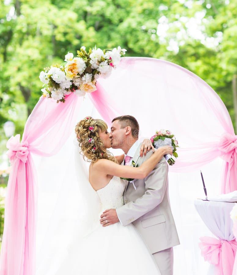 Romantiska par för lycklig nygift person som kysser på bröllopgången med rosa garneringar och blommor arkivfoton