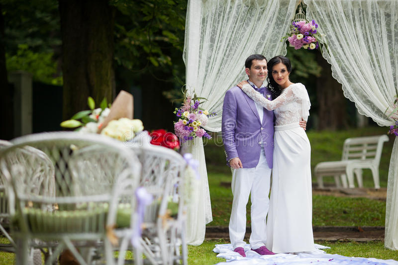 Romantiska par för nygift person som kramar på gången för bröllopceremoni royaltyfri bild