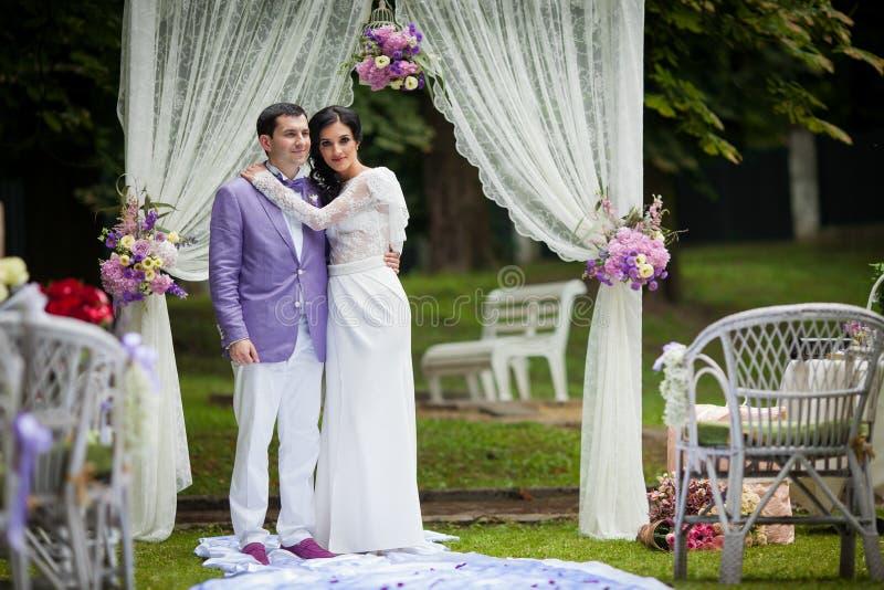 Romantiska par för nygift person som kramar på gången för bröllopceremoni royaltyfria bilder