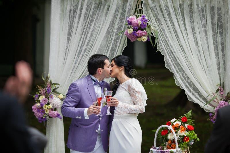 Romantiska par för nygift person som kysser och dricker champagne på weddien royaltyfri foto