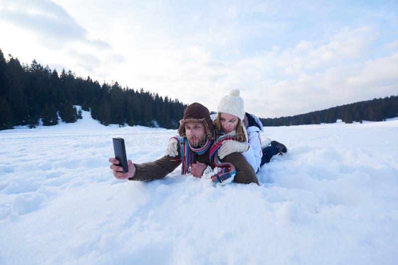 Romantiska par har gyckel i ny snö och taselfie royaltyfri fotografi