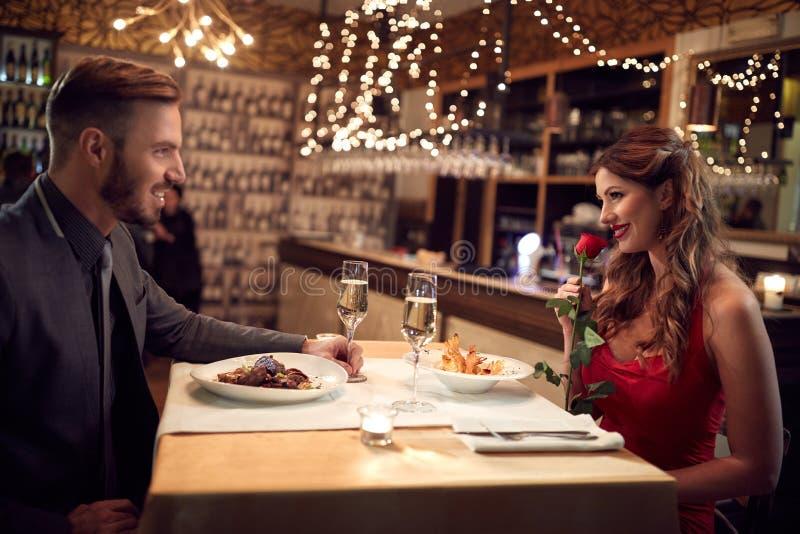 Romantiska par har matställen i restaurang royaltyfri foto