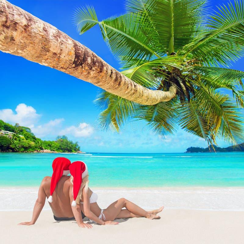 Romantiska par i röd juljultomten som hattar solbadar på tropiskt, gömma i handflatan den sandiga östranden royaltyfri bild