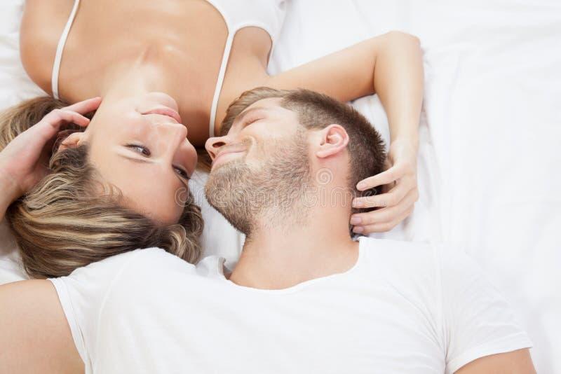 Romantiska par i säng arkivfoto