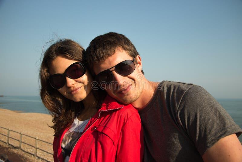 Romantiska par i sunglases på stranden, blå bakgrund royaltyfria foton