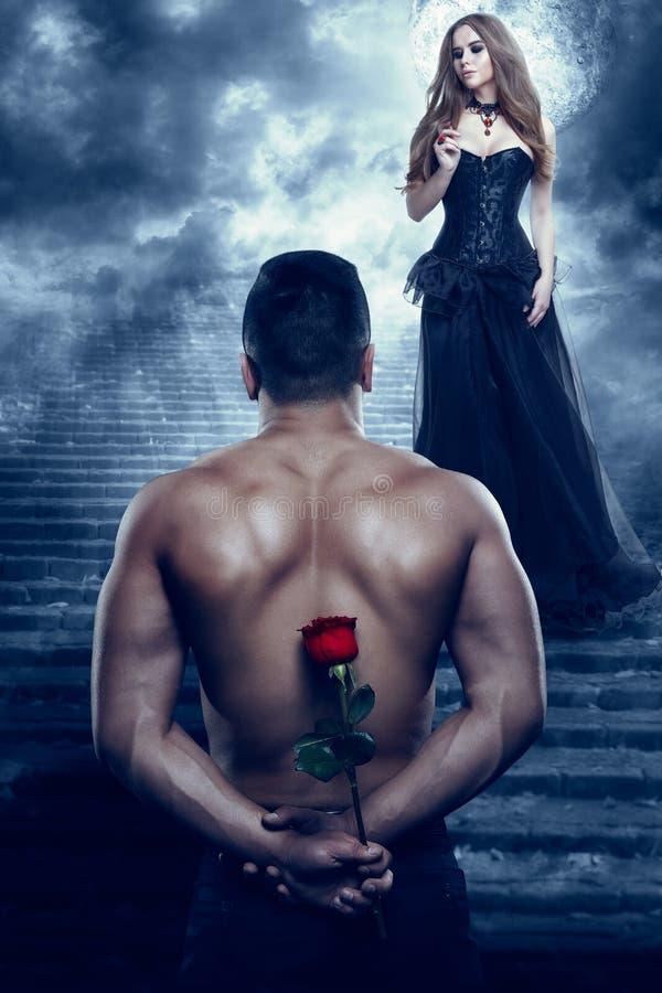 Romantiska par, man ger blomman till den härliga kvinnan, idrotts- rymmande ros för sexig vän arkivfoto