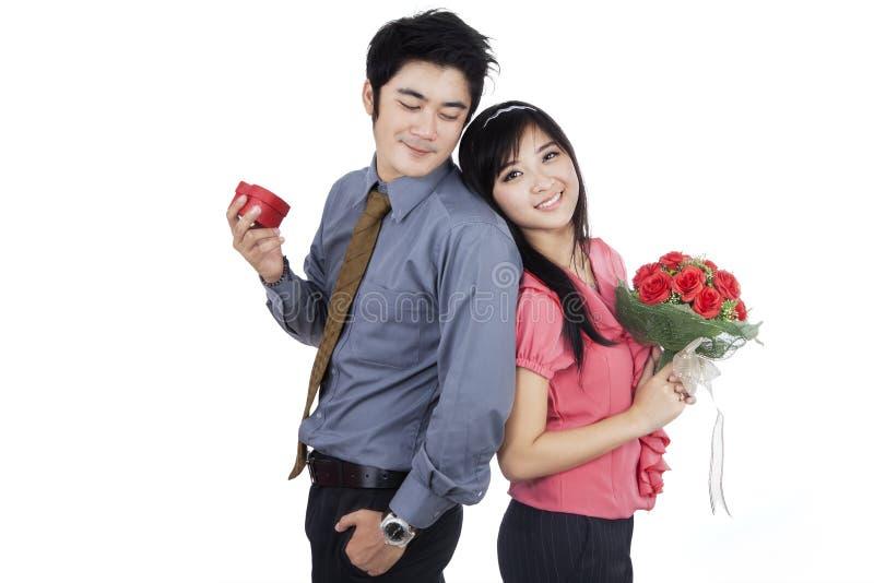 Romantiska par med blommor och Giftbox royaltyfri foto