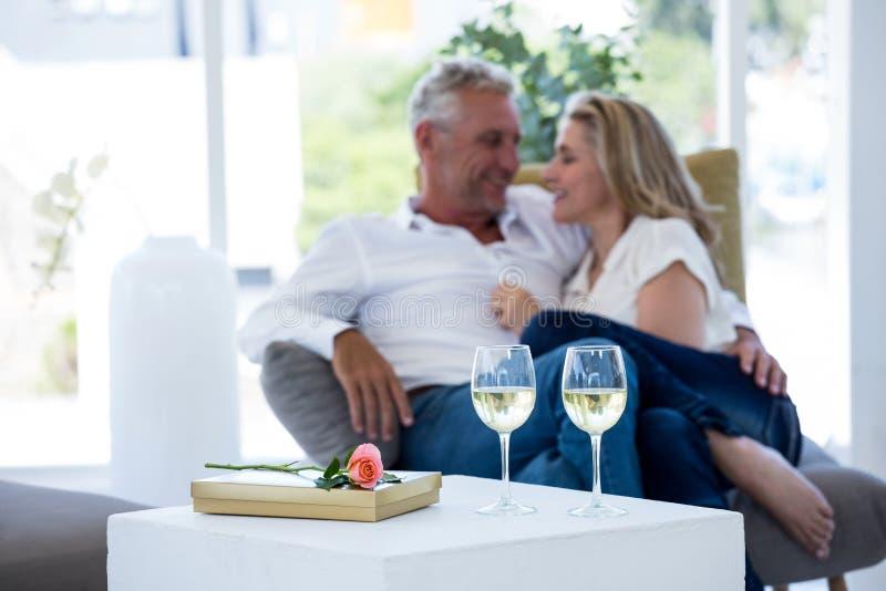 Romantiska par med exponeringsglas för vitt vin vid den rosa och gåvaasken på tabellen royaltyfri bild