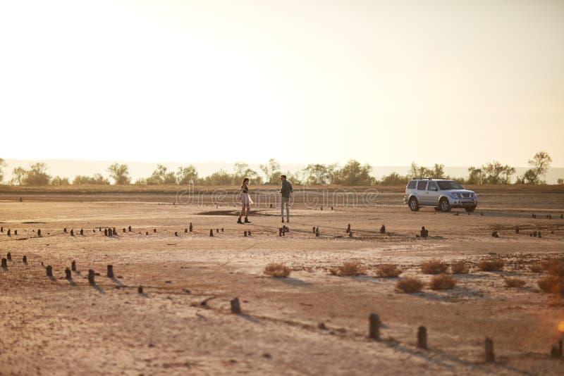 Romantiska par near bilen på en naturlig bakgrund Resande begrepp för naturlig landskapbil kopiera avstånd royaltyfri foto