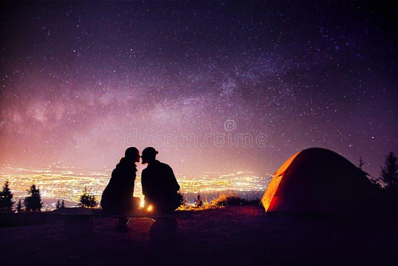 Romantiska par near lägereld på stjärnklar himmel arkivfoto