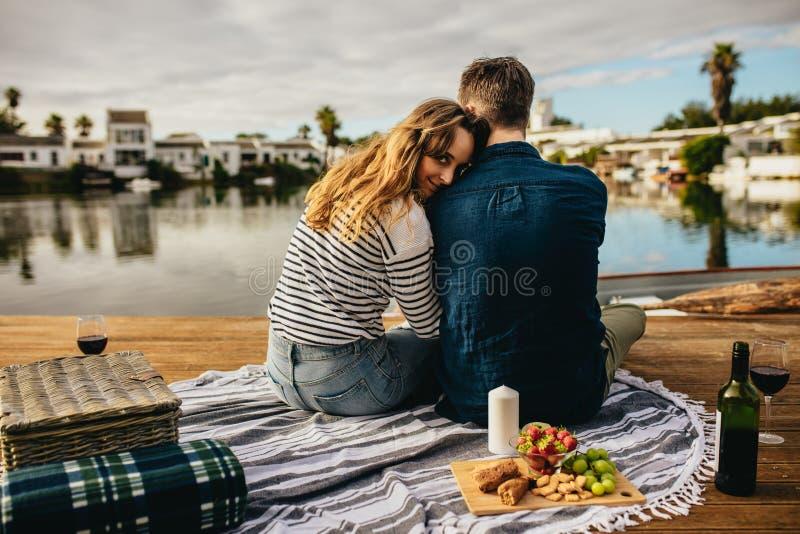 Romantiska par på ett datum som sitter nära en sjö med mellanmål arkivbild