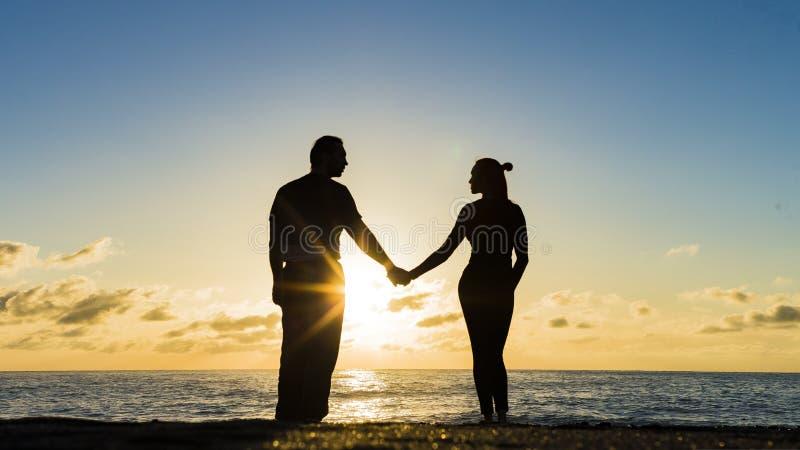 Romantiska par på stranden på den färgrika solnedgången på bakgrund fotografering för bildbyråer