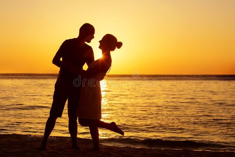 Romantiska par på stranden på den färgrika solnedgången på bakgrund royaltyfri fotografi