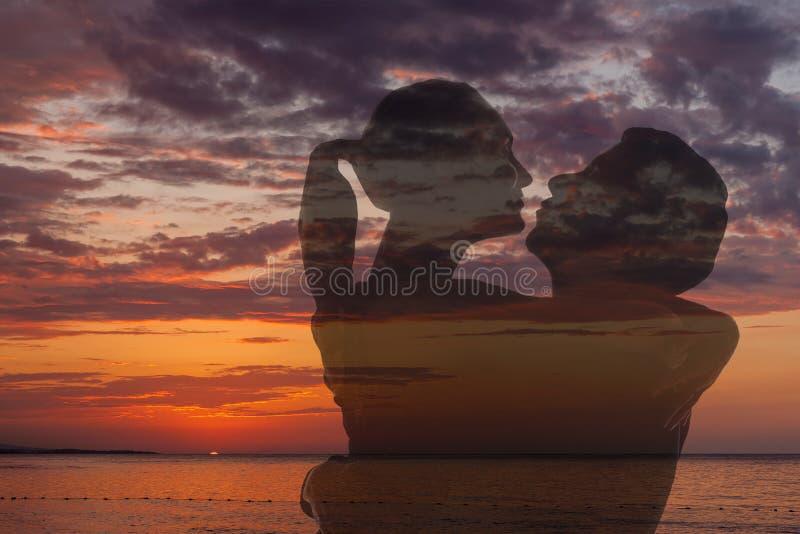 Romantiska par på stranden på den färgrika solnedgången fotografering för bildbyråer