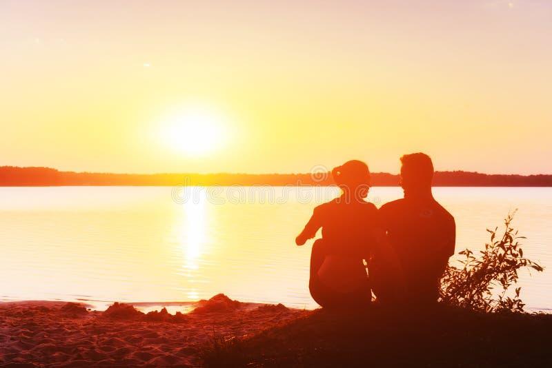 Romantiska par på stranden på den färgrika solnedgången på bakgrund royaltyfria foton