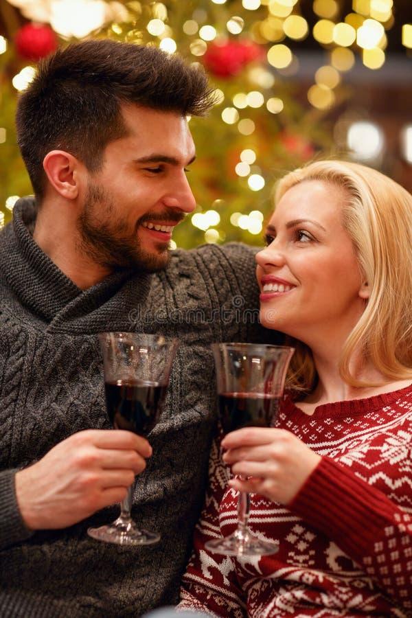 Romantiska par som firar jul som rostar med exponeringsglas av r arkivbilder