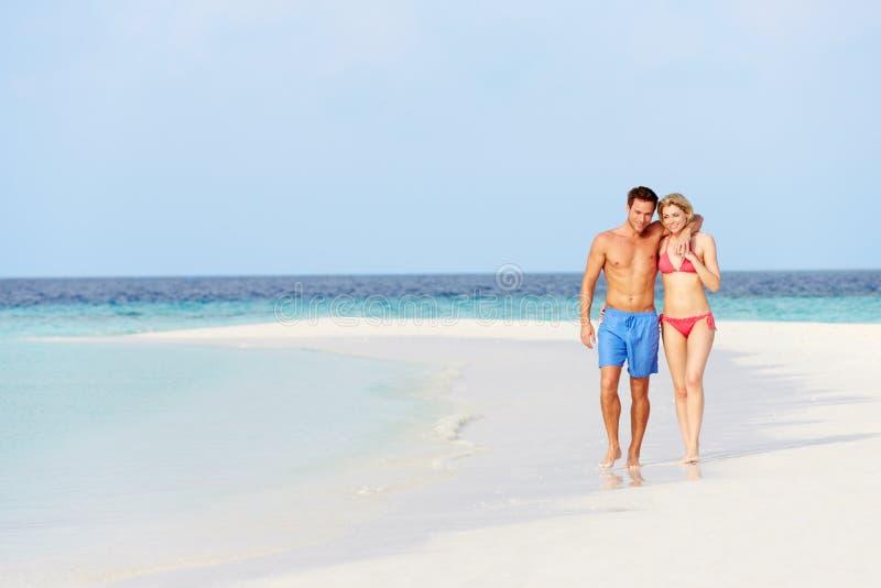 Romantiska par som går på den härliga tropiska stranden arkivbild