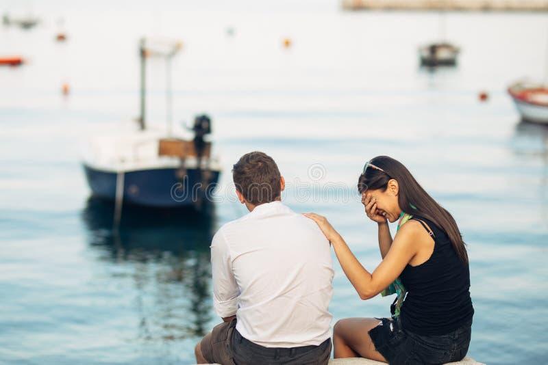 Romantiska par som har förhållandeproblem Kvinnagråt och tiggeri en man Fiskareliv, farlig ockupation Marinsjömän royaltyfria foton