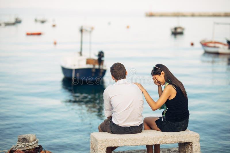 Romantiska par som har förhållandeproblem Kvinnagråt och tiggeri en man Fiskareliv, farlig ockupation Marinsjömän royaltyfria bilder