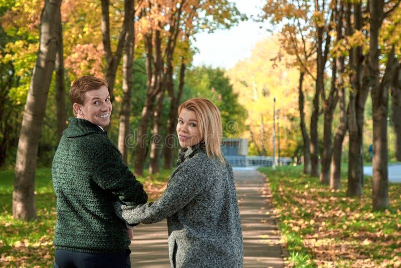 Romantiska par som kopplar av i höst, parkerar, keln som tycker om ny luft, den härliga naturen, trevligt nedgångväder älsklingen royaltyfria foton