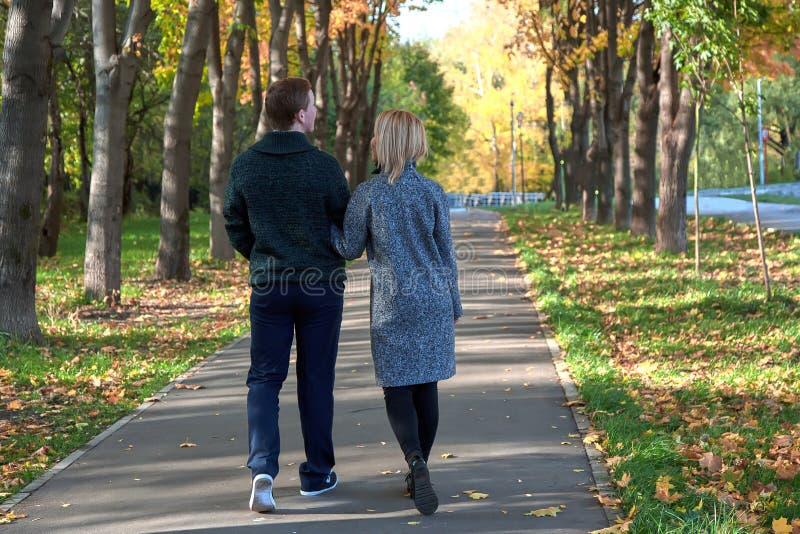 Romantiska par som kopplar av i höst, parkerar, keln som tycker om ny luft, den härliga naturen, trevligt nedgångväder älsklingen arkivfoto