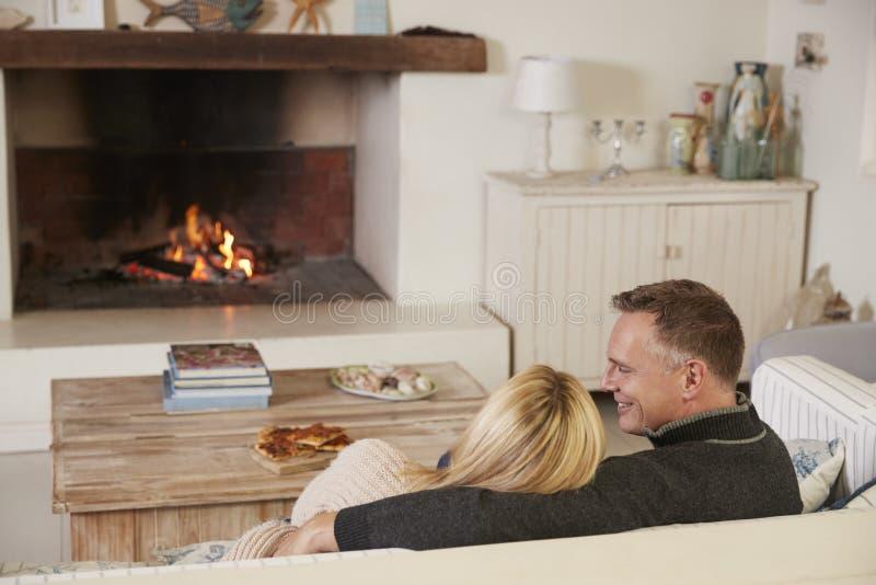 Romantiska par som kopplar av i vardagsrum bredvid öppen brand arkivbilder